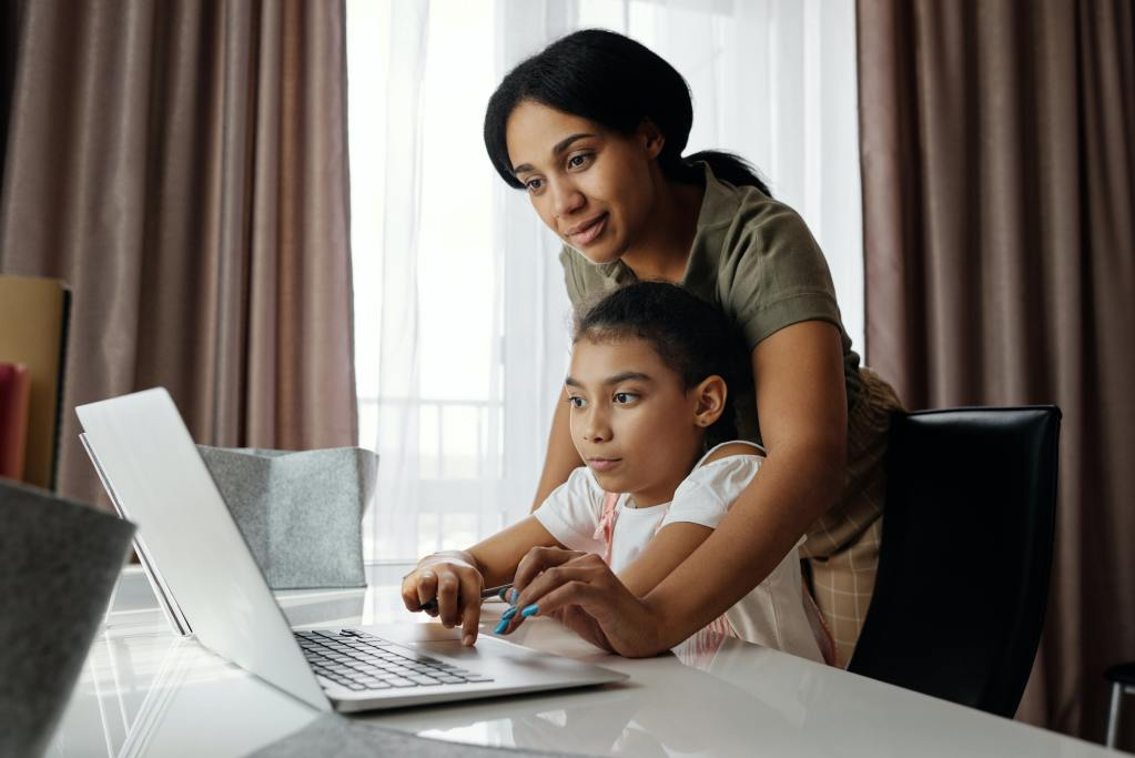 A mother helping her child on the computer before her pediatric telehealth session.